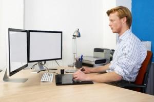 An zwei Monitoren arbeiten